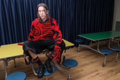 DANCING IN THE EYE OF THE HURRICANE ph. Lorenzo Marcucci for Collectible DRY Armand wears cotton sweater, Stella McCartney, sleeveless shirt and wool pants with straps, Dior Homme, socks, Vetements, sneakers, Versace.