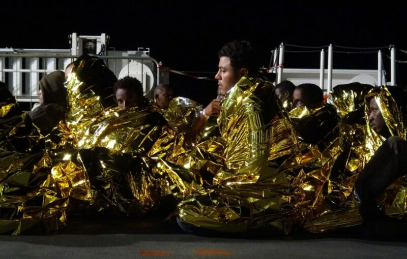 MOTIONLESS IN THEIR THOUGHTS. REFUGEES WRAPPED IN THERMAL BLANKETS